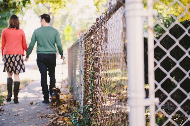 engaged couple walking dog beside chain link fence