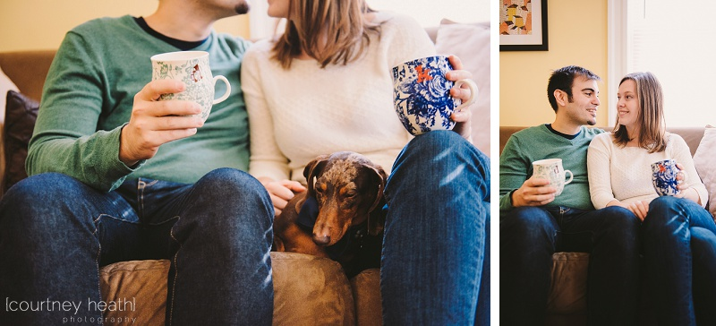 in home lifestyle engagement session couple holding coffee mugs on couch with dog
