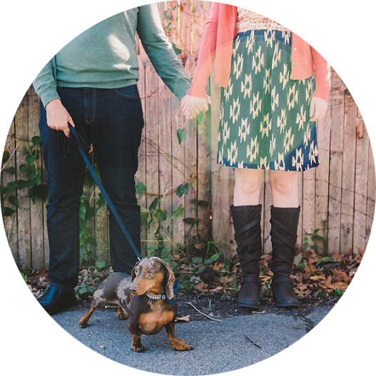 engaged couple holding hands with dog on leash in front of fence