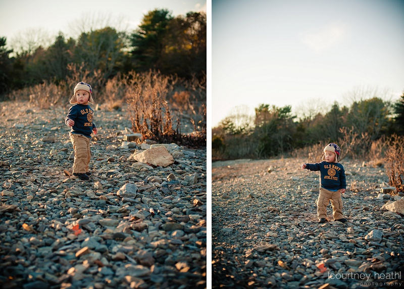 Boy with pilot hat playing on rocks at the beach during sunset