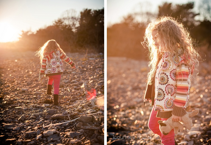 Long curly haired girl at the beach at sunset with lens flare