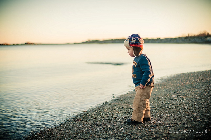 Young boy wearing pilot hat standing next to ocean water