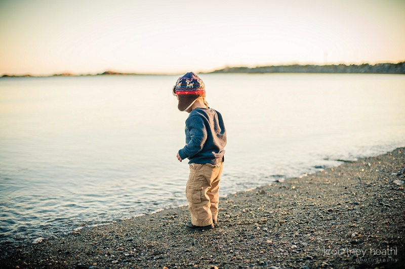 Young boy wearing pilot hat standing next to ocean water