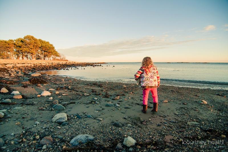 Young girl standing next to ocean water