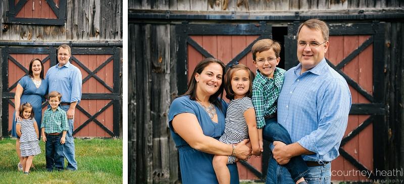 family in front of red barn door