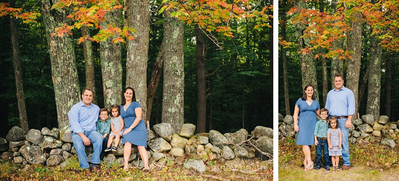 family posing near stone wall and fall foliage