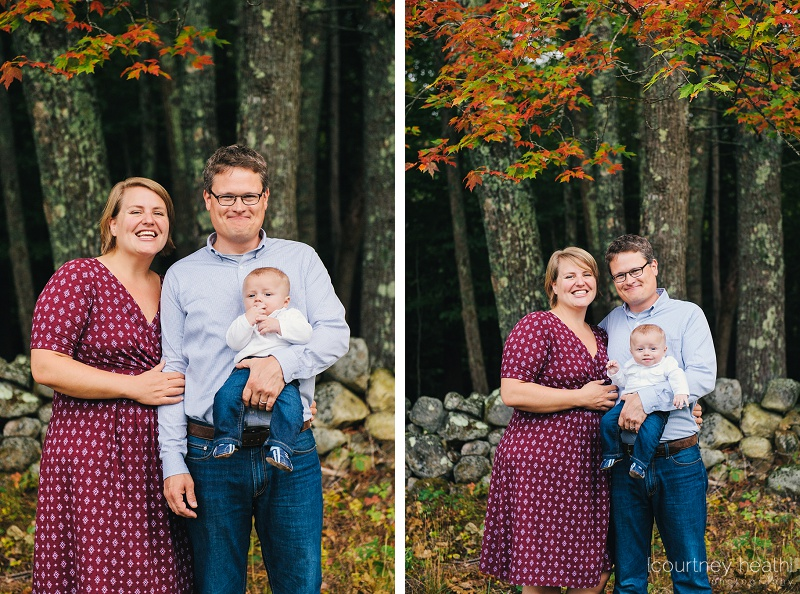 Family in front of stone wall and fall foliage
