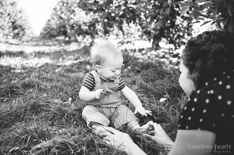 Black and white mother smiling at baby in apple orchard