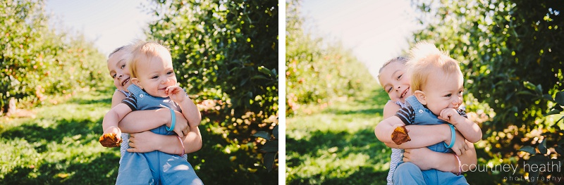 Big sister holding little brother at apple orchard