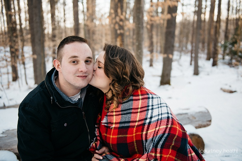 Fiancee kisses fiance's cheek in snowy NH woods