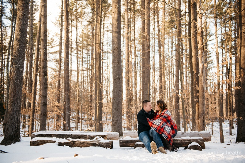 engaged couple cuddling on a log in snowy new hampshire woods