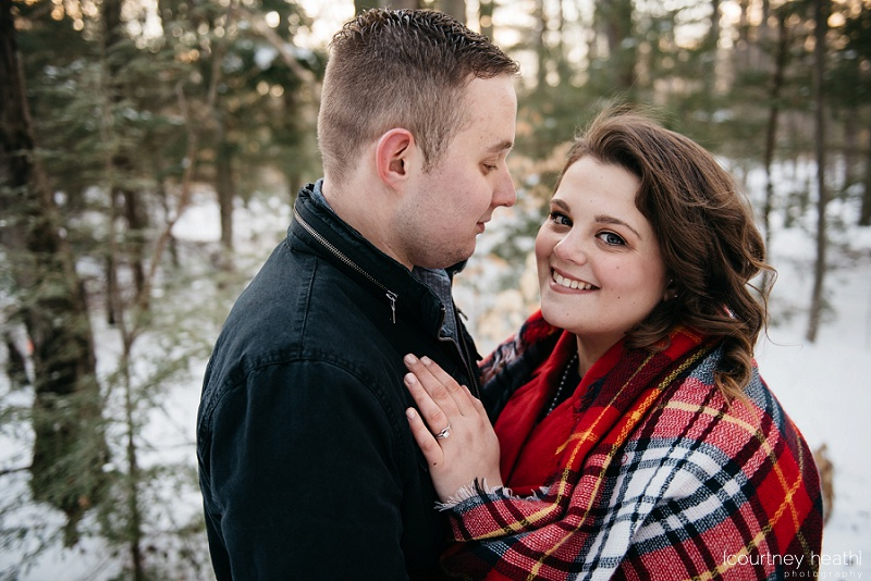 engaged couple cuddling under plaid blanket