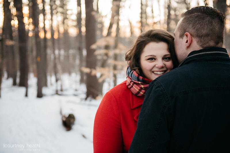 Couple cuddling in snowy NH woods
