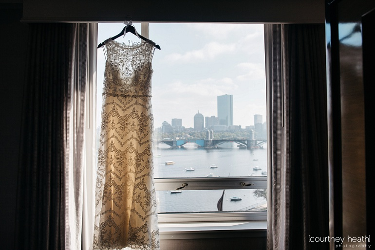 Wedding dress hangs in window with Boston skyline in the back at Royal Sonesta