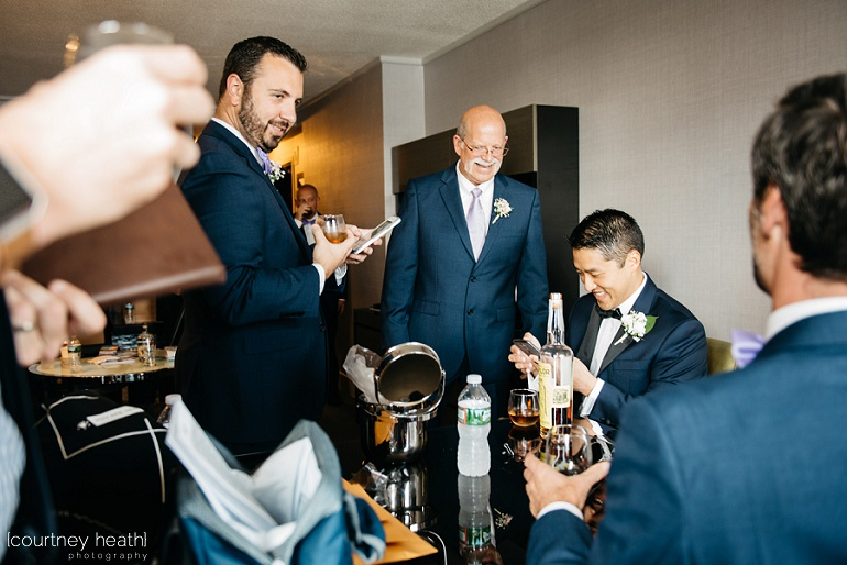 Groom and groomsmen hold their iPhones inside room at Royal Sonesta Boston