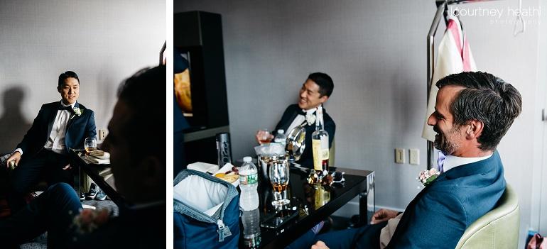 Groom and groomsmen laugh inside hotel room at Royal Sonesta Boston