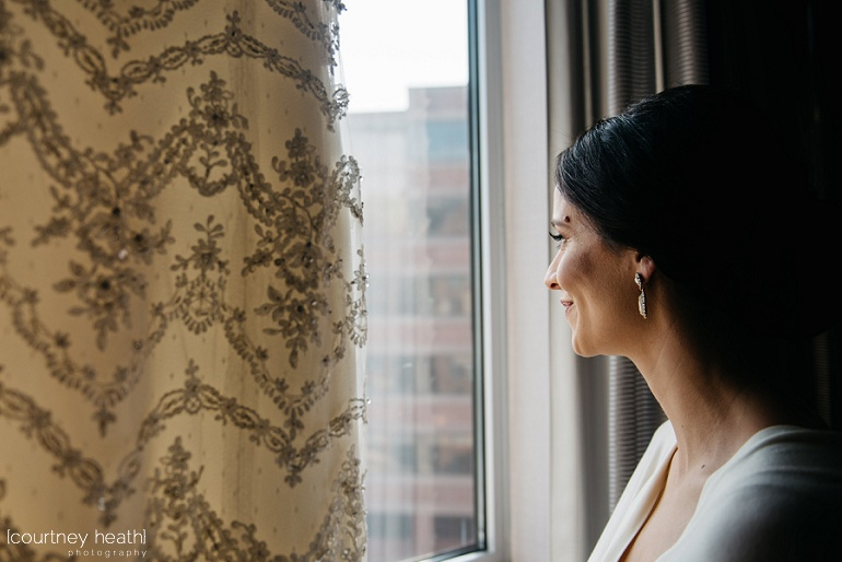 Bride smiles looking out Royal Sonesta Boston window