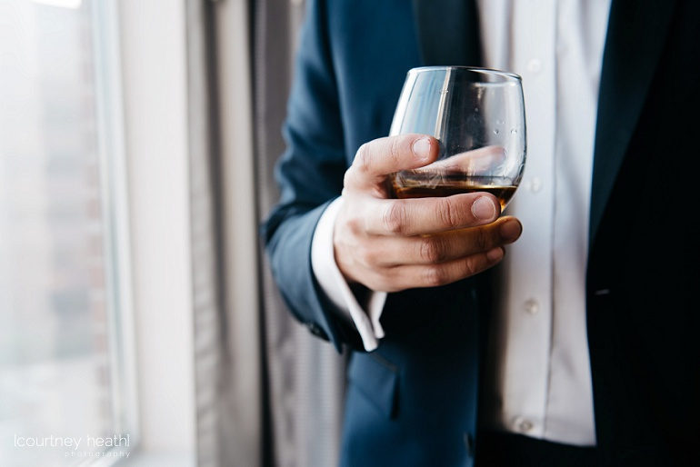 Groom holds glass of Taylor bourbon
