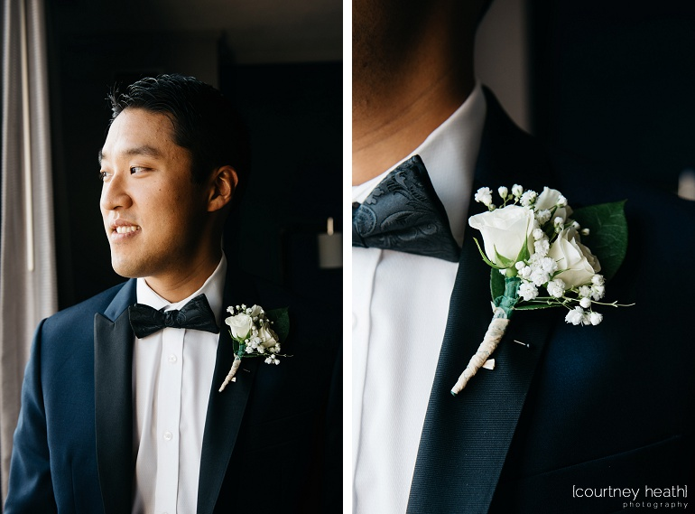 Groom wearing black bow tie and white rose boutineer looks out window at Royal Sonesta Boston