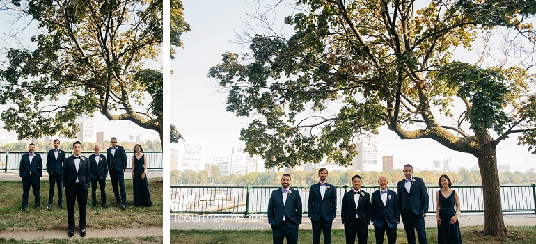 Groom and groomsmen stand beneath tree at Charles River outside of Royal Sonesta Boston