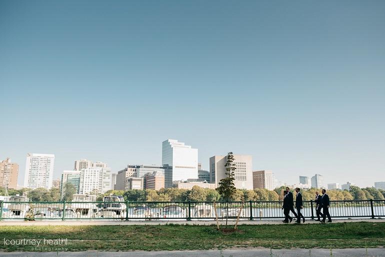 Groomsmen walk along Charles River Boston