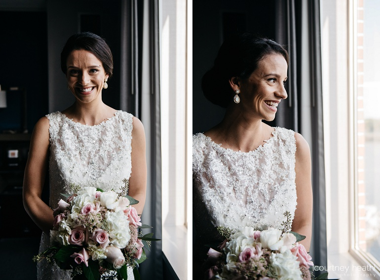 Stunning bride holding rose bouquet smiles beside window at Royal Sonesta Boston