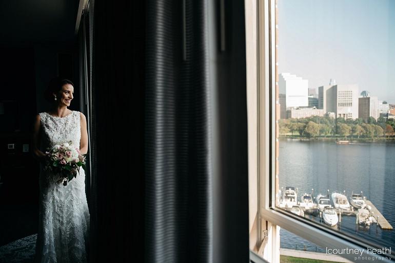 Bride smiles looking out window at Royal Sonesta Boston