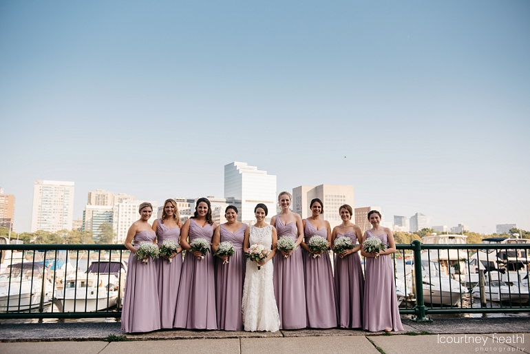 Bride and bridesmaids stand in front of Charles River and Boston skyline