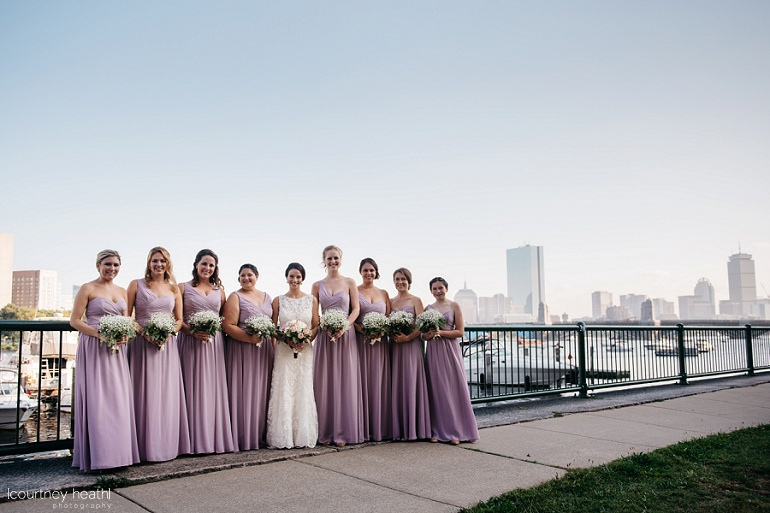 Bride and bridesmaids stand beside Charles River with Boston skyline behind