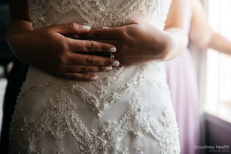 Bride clasps hands against stomach