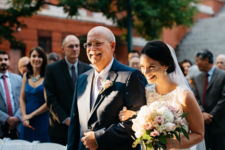 Bride smiles big at her groom as she holds her father's arm