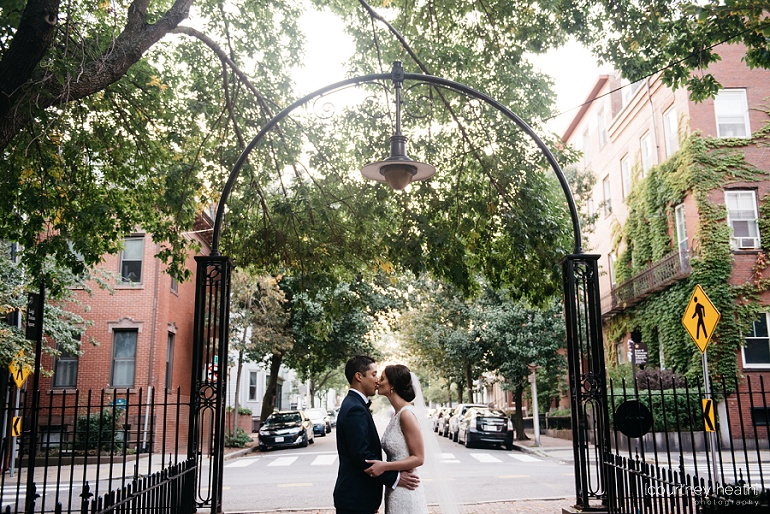 Bride and Groom kiss under wrought iron arch Cambridge Multicultural Arts Center Boston